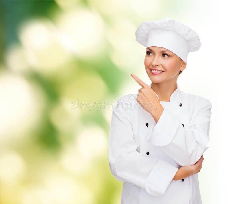 Glimlachende vrouwelijke chef-kok die vinger richten aan het sonething stock foto's