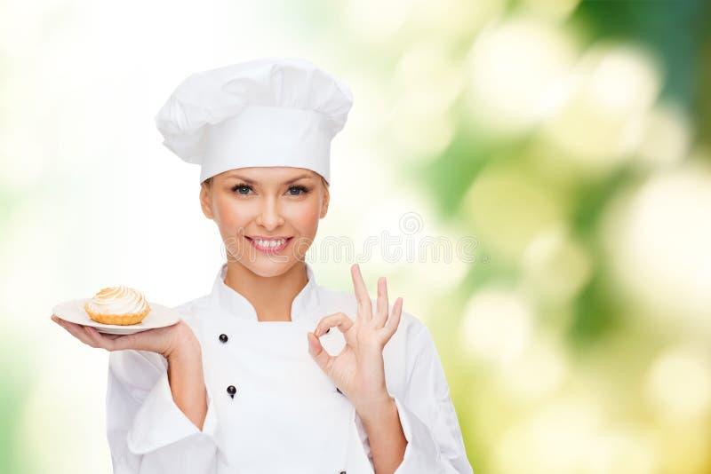 Glimlachende vrouwelijke chef-kok met cake op plaat royalty-vrije stock afbeelding
