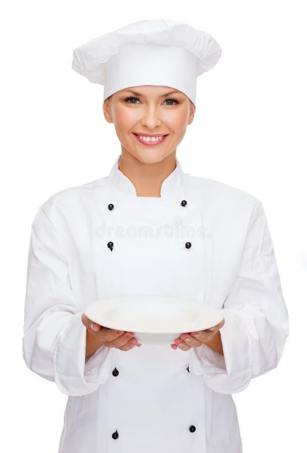 Glimlachende vrouwelijke chef-kok met lege plaat stock foto's