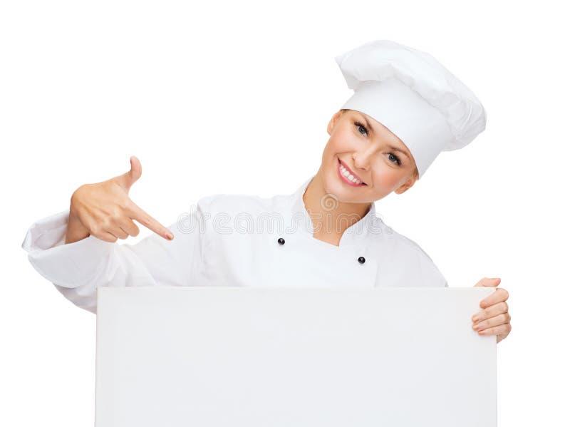 Glimlachende vrouwelijke chef-kok met witte lege raad royalty-vrije stock afbeeldingen