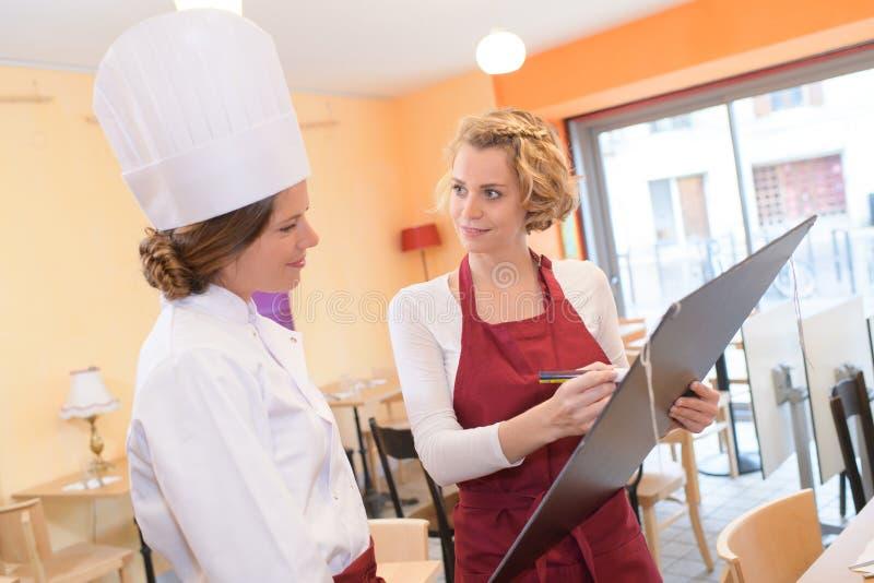 Glimlachende vrouwelijke chef-kokkok of bakker met leeg zwart menu stock foto