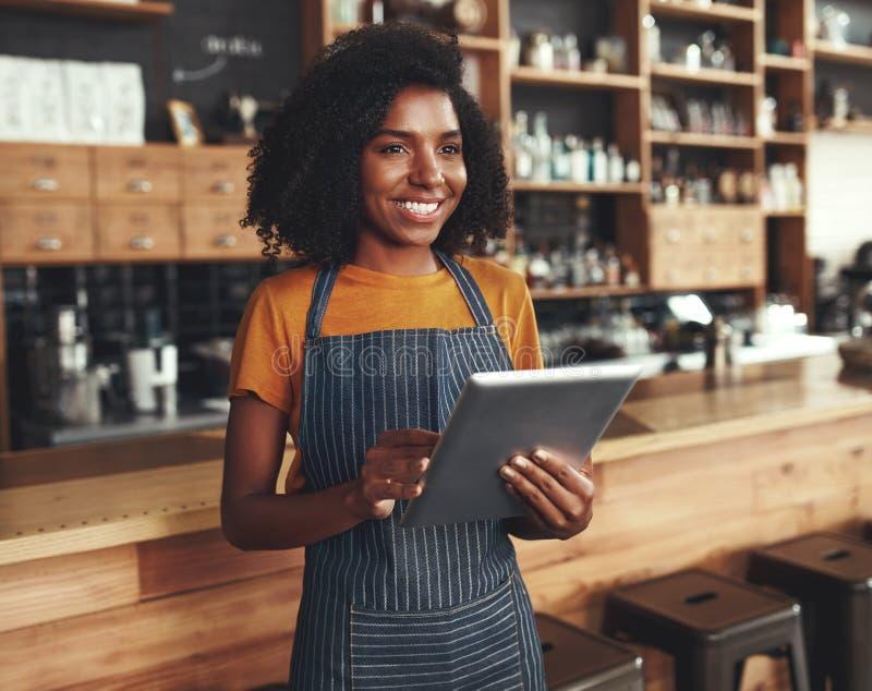 Glimlachende vrouwelijke eigenaar die bij haar koffiewinkel digitale tablet houden royalty-vrije stock foto's
