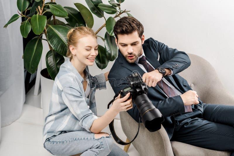 glimlachende vrouwelijke fotograaf en verraste knappe zakenman die camera met behulp van royalty-vrije stock fotografie