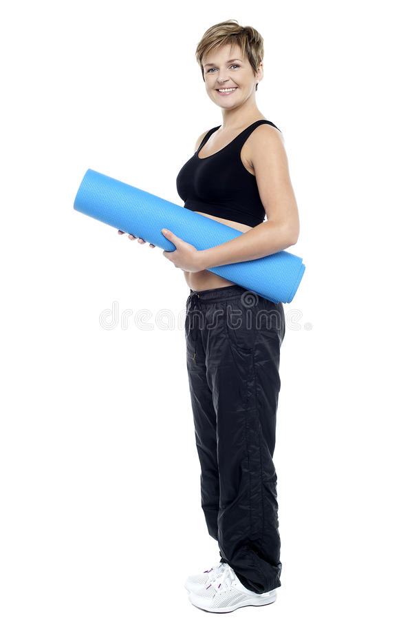 Glimlachende vrouwelijke instructeur die een blauwe yogamat draagt stock afbeeldingen