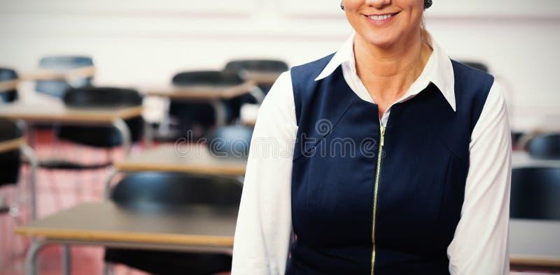 Glimlachende vrouwelijke leraar in de klassenruimte royalty-vrije stock afbeeldingen