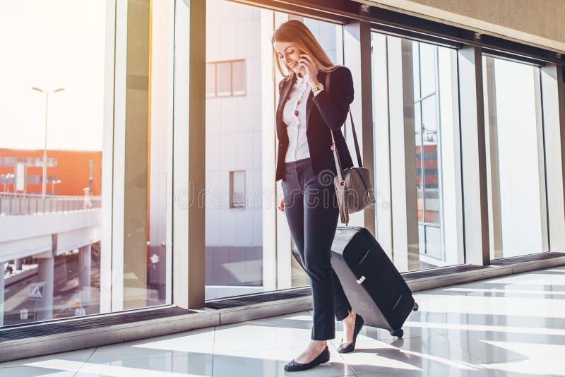 Glimlachende vrouwelijke passagier die aan uitgangspoort te werk gaan die koffer trekken door luchthavensamenkomst terwijl het sp royalty-vrije stock afbeeldingen