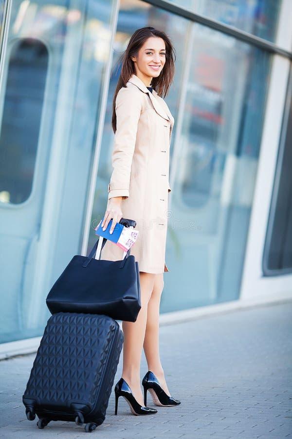 Glimlachende vrouwelijke passagier die aan uitgangspoort te werk gaan die koffer trekken door luchthavensamenkomst royalty-vrije stock foto