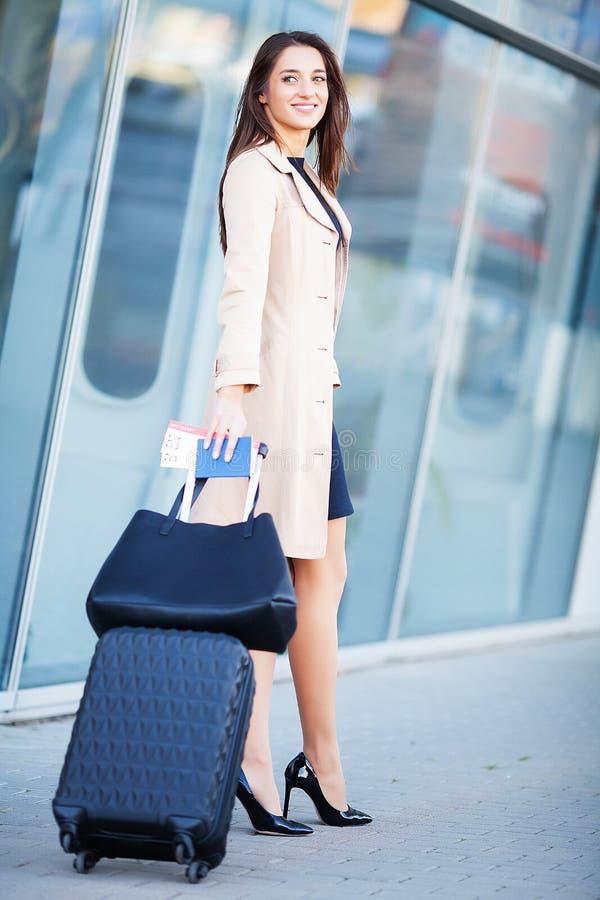 Glimlachende vrouwelijke passagier die aan uitgangspoort te werk gaan die koffer trekken door luchthavensamenkomst stock fotografie