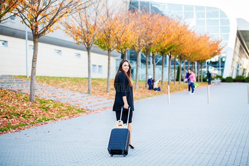 Glimlachende vrouwelijke passagier die aan uitgangspoort te werk gaan die koffer trekken door luchthavensamenkomst royalty-vrije stock afbeelding