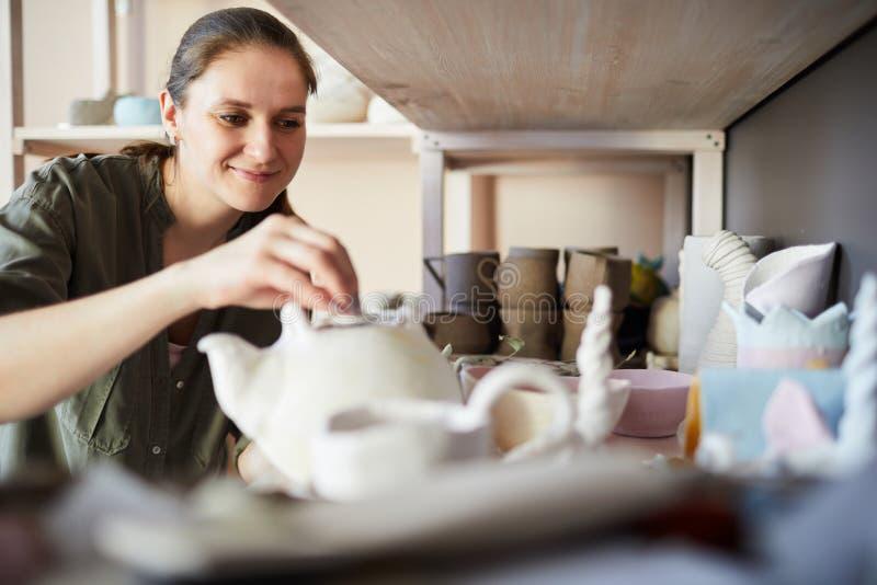 Glimlachende Vrouwelijke Pottenbakker in Bergruimte stock foto's