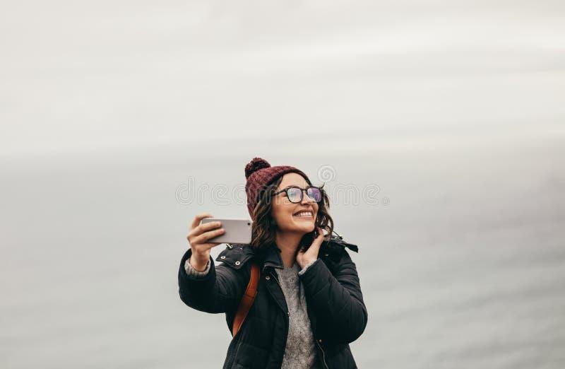 Glimlachende vrouwelijke reiziger die een selfie nemen tegen oceaan stock afbeelding