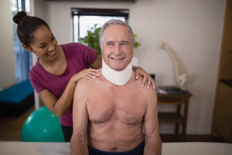Glimlachende vrouwelijke therapeut die hogere mannelijke patiënt met halskraag bekijken royalty-vrije stock foto