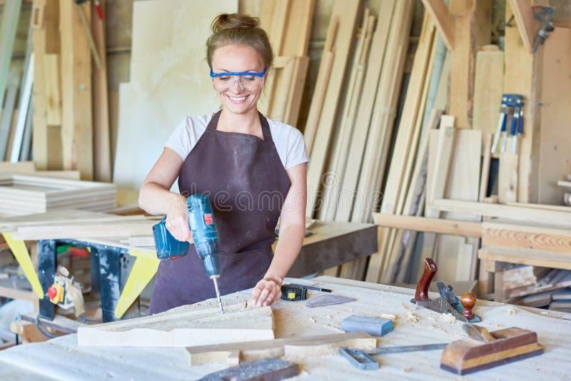 Glimlachende Vrouwelijke Timmerman Working in Winkel stock afbeelding