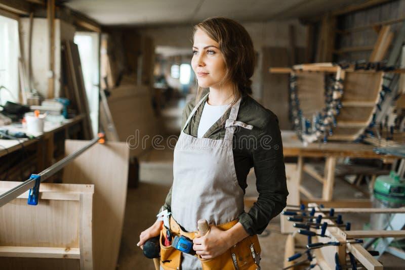 Glimlachende vrouwelijke timmerman in workshop stock foto's
