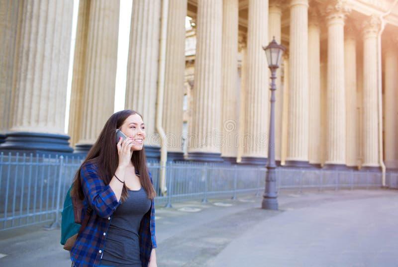 Glimlachende vrouwelijke toerist die het gesprek van de celtelefoon hebben dichtbij de oude architecturale bouw royalty-vrije stock foto's