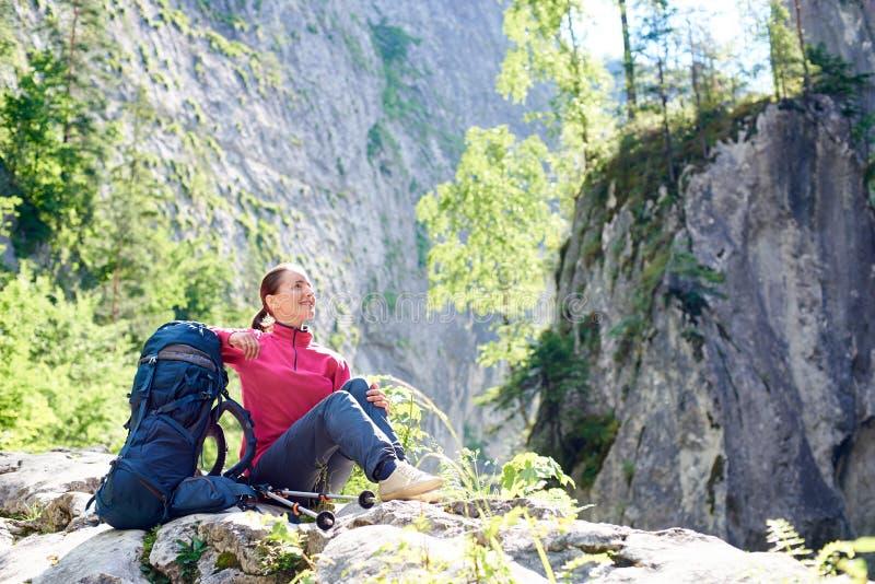 Glimlachende vrouwelijke toerist die op rots het bewonderen schoonheid van adembenemende rotsachtige bergen in spectaculaire plaa royalty-vrije stock foto's