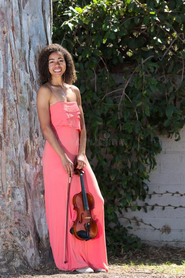 Glimlachende vrouwelijke violist in lange roze kleding buiten stock fotografie
