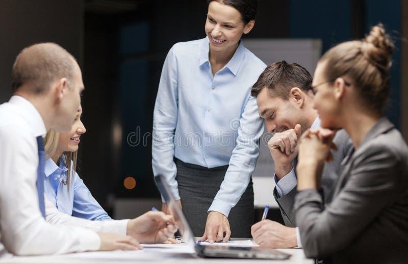 Glimlachende vrouwelijke werkgever die aan commercieel team spreken royalty-vrije stock afbeeldingen