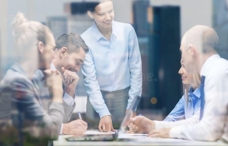 Glimlachende vrouwelijke werkgever die aan commercieel team spreken royalty-vrije stock afbeelding