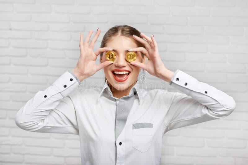 Glimlachende vrouwelijke werknemer die in witte slimme blouse gouden bitcoins voor haar ogen zetten royalty-vrije stock foto's