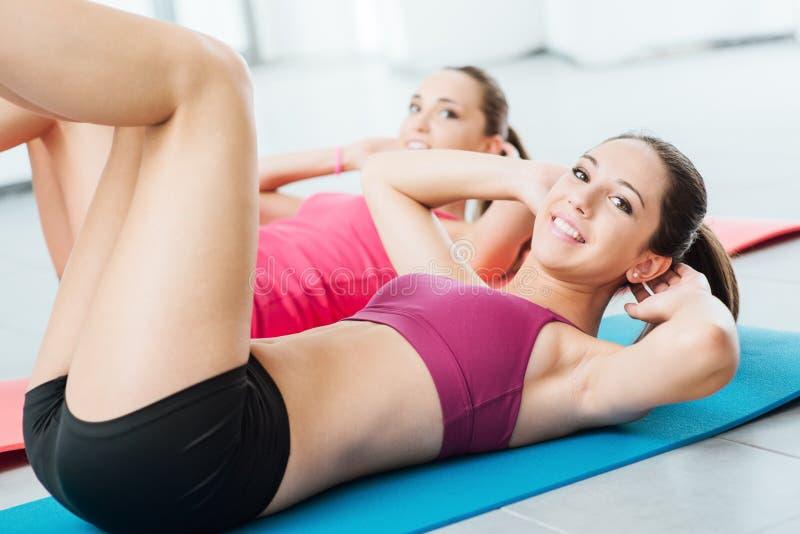 Glimlachende vrouwen die bij de gymnastiek uitoefenen stock foto's