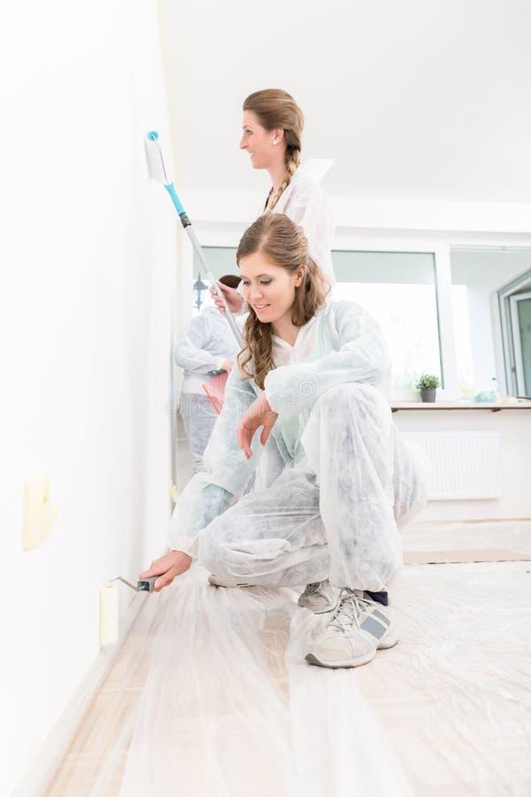 Glimlachende vrouwen die de muur met rol schilderen stock afbeelding