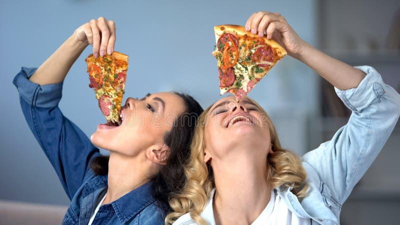 Glimlachende vrouwen die greedily smakelijke pizza, snel voedselverslaving, ongezond dieet eten royalty-vrije stock afbeeldingen