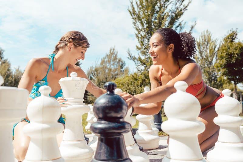 Glimlachende vrouwen die groot schaak spelen royalty-vrije stock foto
