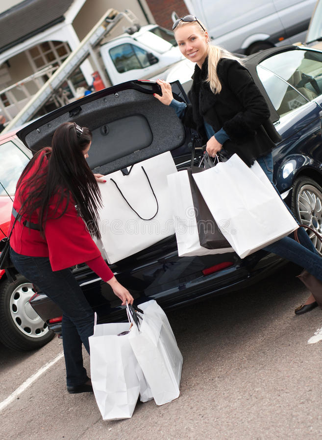 Glimlachende vrouwen die het winkelen zakken zetten in de auto stock afbeeldingen
