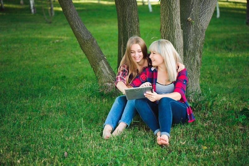 Glimlachende vrouwen die tablet ps op een groene weide gebruiken stock afbeeldingen
