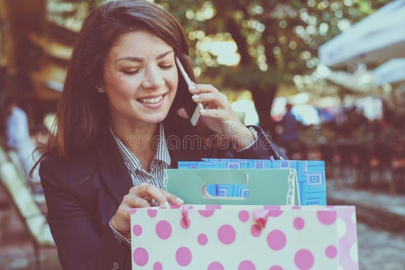 Glimlachende vrouwen sprekende telefoon, die in het winkelen zakken kijken royalty-vrije stock foto