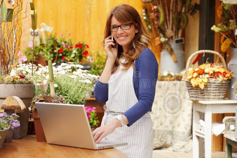 Glimlachende Vrouwenbloemist, van de Kleine de Eigenaar Bedrijfsbloemwinkel stock foto's