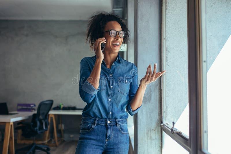 Glimlachende vrouwenondernemer die over telefoon spreken stock afbeeldingen