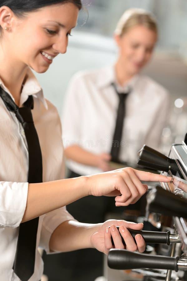 Glimlachende vrouwenserveerster die koffiemachine voorbereiden stock afbeelding