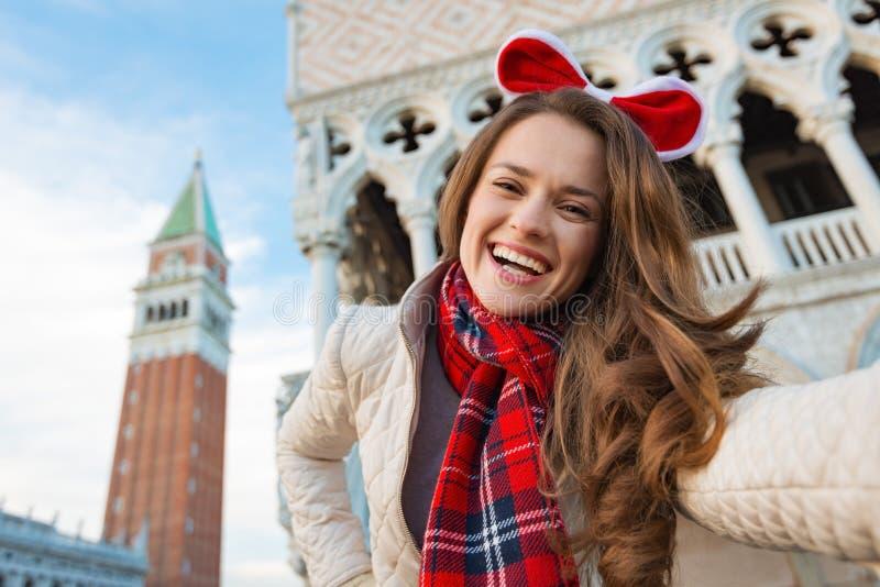 Glimlachende vrouwentoerist die Kerstmis selfie in Venetië, Italië nemen stock foto