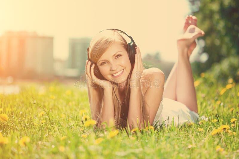 Glimlachende vrouwenvrouw die aan muziek op hoofdtelefoons in openlucht luisteren royalty-vrije stock afbeeldingen