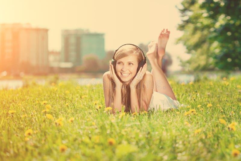 Glimlachende vrouwenvrouw die aan muziek op hoofdtelefoons in openlucht luisteren royalty-vrije stock foto