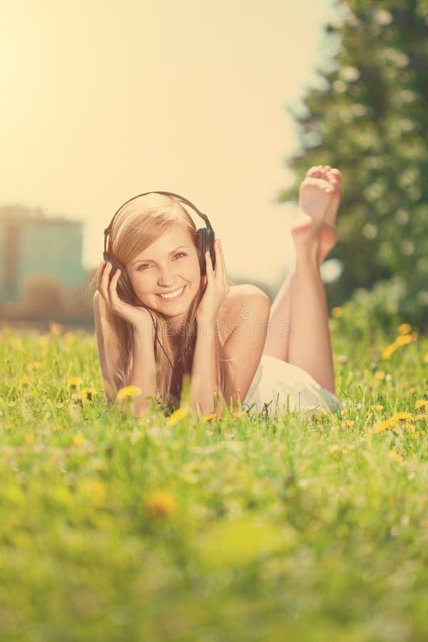 Glimlachende vrouwenvrouw die aan muziek op hoofdtelefoons in openlucht luisteren royalty-vrije stock fotografie