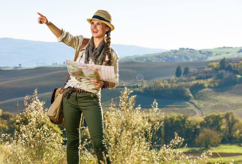 Glimlachende vrouwenwandelaar die in de holding van Toscanië kaart en het richten wandelen royalty-vrije stock afbeelding