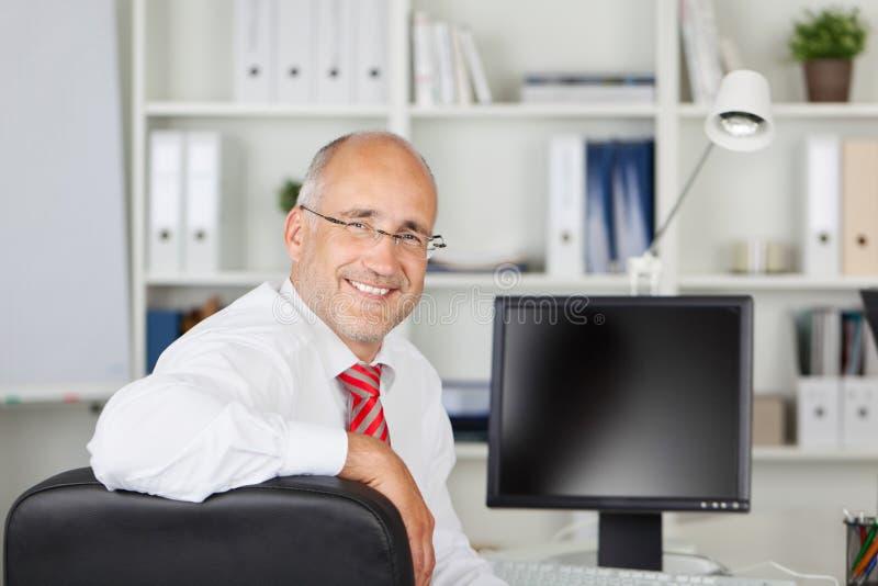 Glimlachende werknemer die terug kijken stock foto's