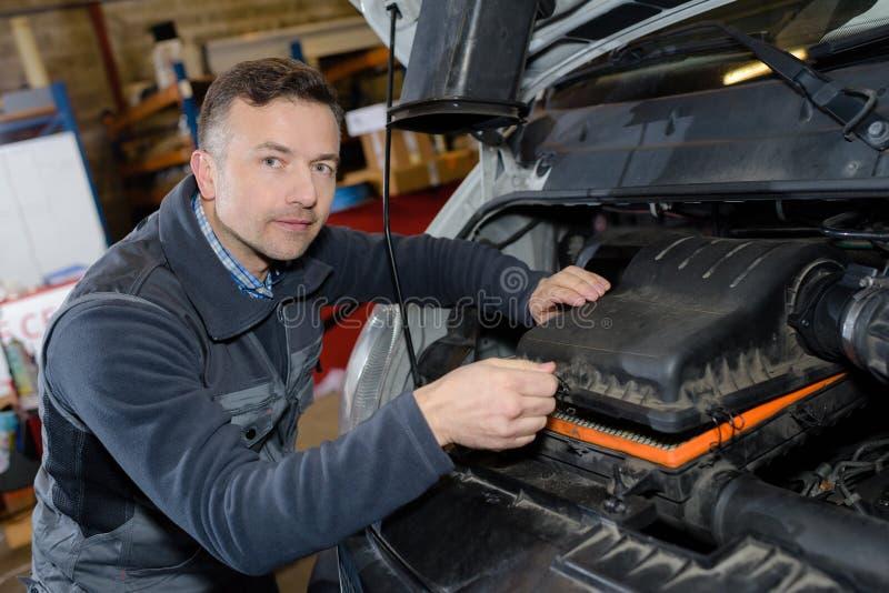 Glimlachende werktuigkundige die motor van een auto in garage herstellen stock foto