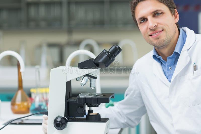 Glimlachende wetenschappelijke onderzoeker met microscoop in laboratorium stock afbeelding