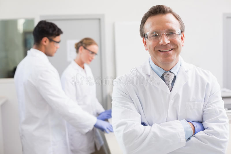 Glimlachende wetenschapper die camera bekijken terwijl collega's die erachter werken stock fotografie
