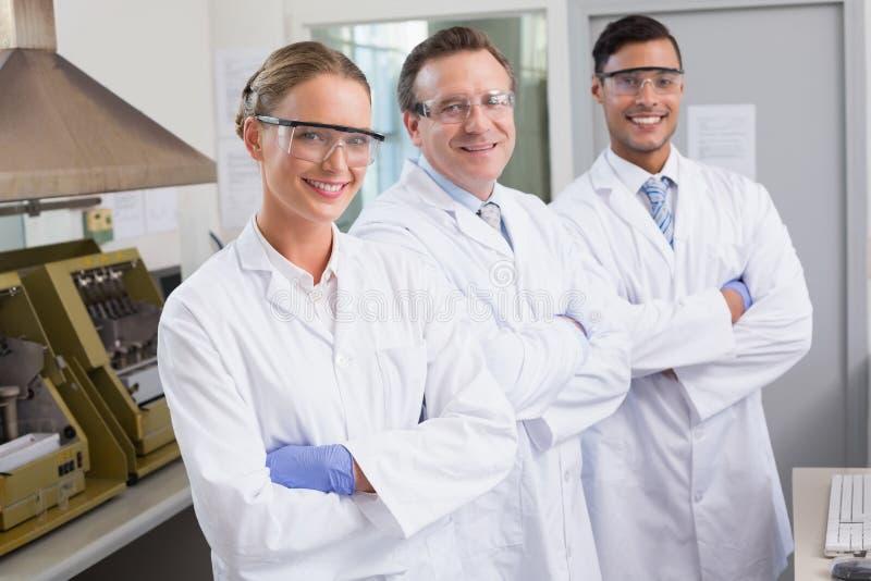 Glimlachende wetenschappers die gekruiste camerawapens bekijken stock afbeelding