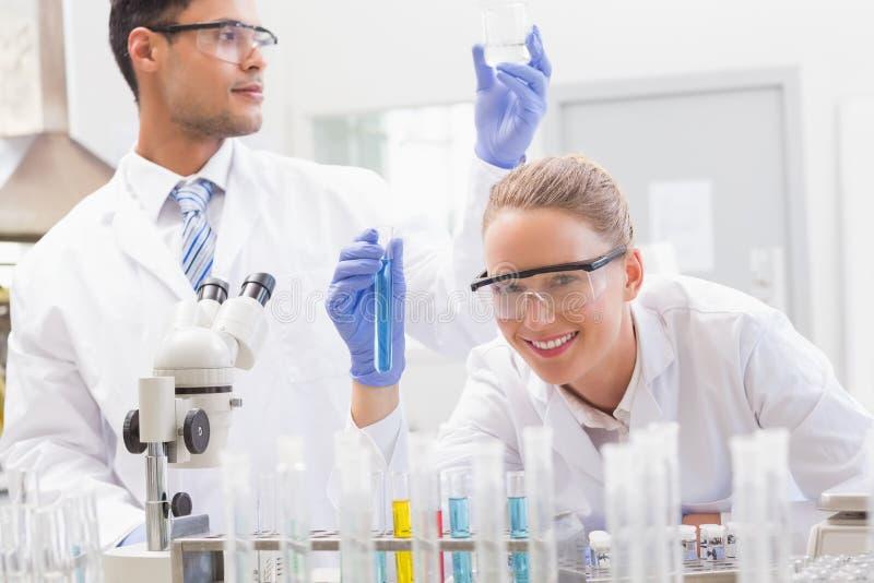 Glimlachende wetenschappers die reageerbuis en beker onderzoeken royalty-vrije stock foto