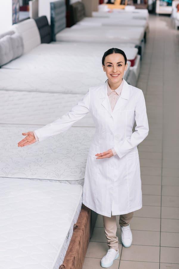 glimlachende winkelmedewerker die in witte laag op orthopedische matrassen richten stock afbeeldingen