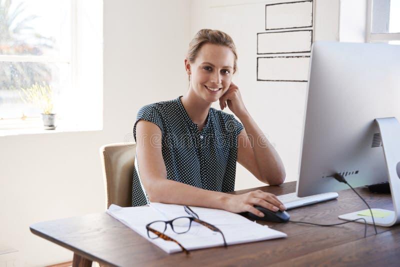 Glimlachende witte vrouw die in een bureau werken die aan camera kijken royalty-vrije stock foto