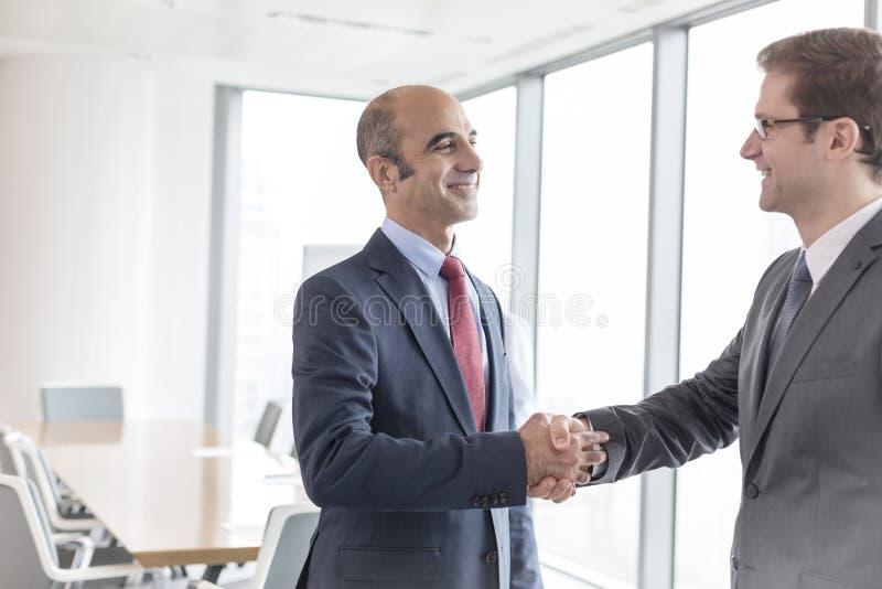 Glimlachende zakenlieden die handen schudden terwijl status in bestuurskamer tijdens vergadering op kantoor stock foto