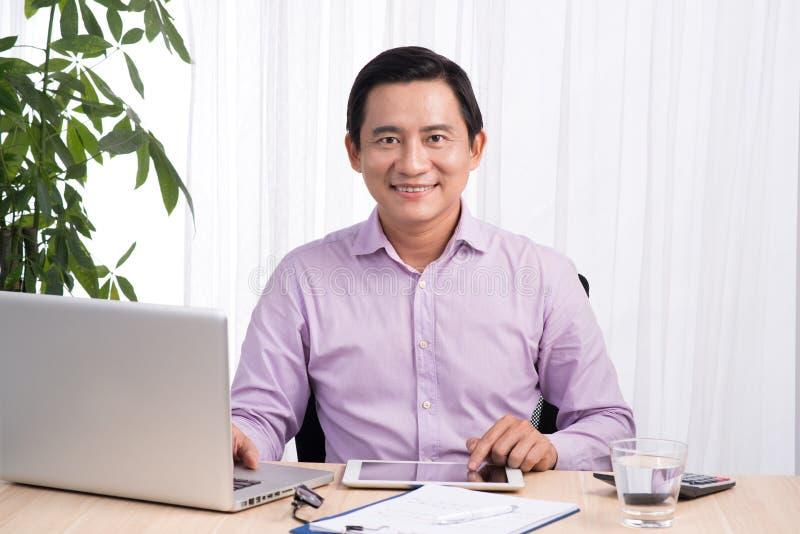 Glimlachende zakenman bij zijn bureau met laptop en documenten in van hem stock foto