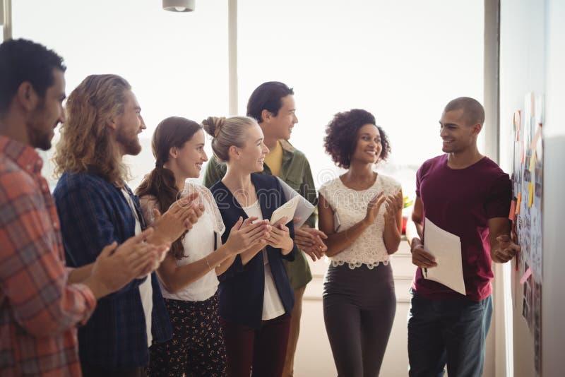 Glimlachende zakenman die aan creatief team op kantoor verklaren royalty-vrije stock afbeelding